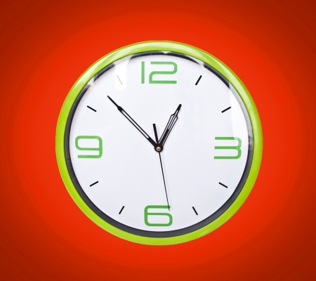 Retro green clock on red background photo