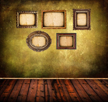 Old room with grunge wall and vintage frames photo