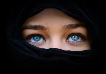 Hermosos ojos azules detrás de la mujer pañuelo negro que mira para arriba Foto de archivo