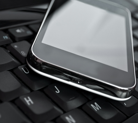 mobile data: Cell phone on laptop keyboard - Business concept
