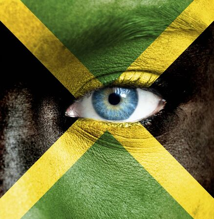 Human face painted with flag of Jamaica photo