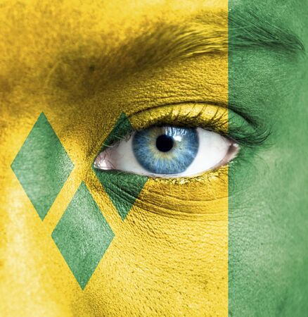 Human face painted with flag of Saint Vincent and the Grenadines Stock Photo - 16523603