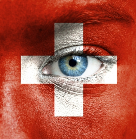 swiss culture: Human face painted with flag of Switzerland Stock Photo
