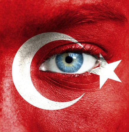 female face closeup: Human face painted with flag of Turkey