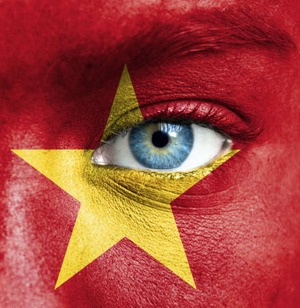 adult vietnam: Human face painted with flag of Vietnam Stock Photo