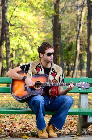 man playing guitar: Man playing guitar on bench in park