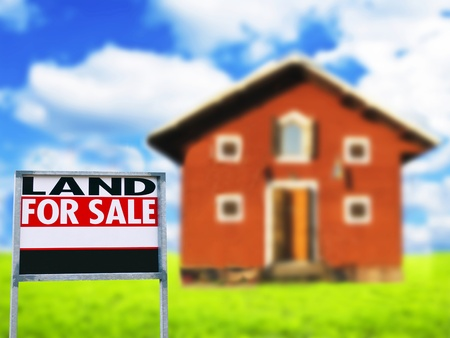 LAND FOR SALE sign against wooden house - Real estate concept photo