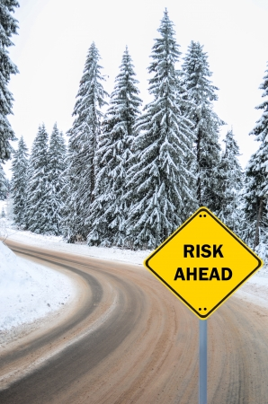 'RISK AHEAD' sign against winter road photo