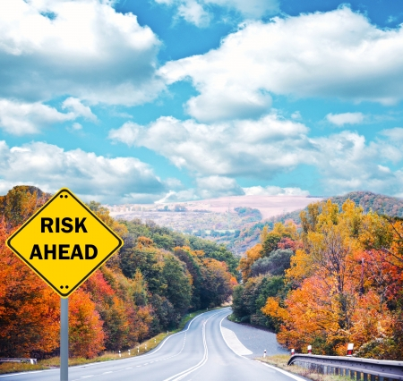 forest management: RISK AHEAD sign against road - Business concept