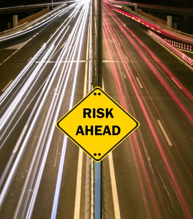 'RISK AHEAD' sign against highway trails photo