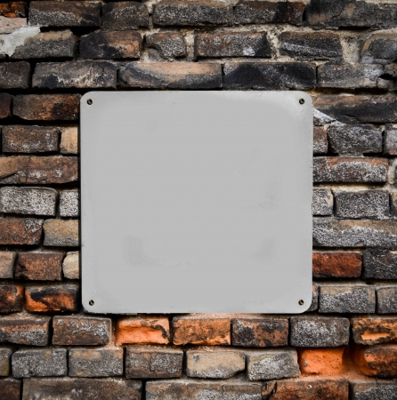 Empty metal sign on brick wall photo