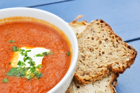 Tomato soup with basil and fresh black bread closeup photo