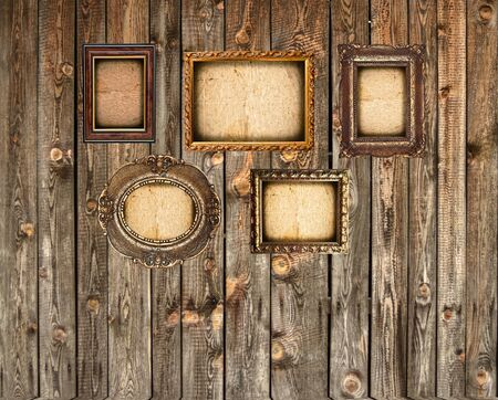 Set of empty picture frames on wooden wall photo