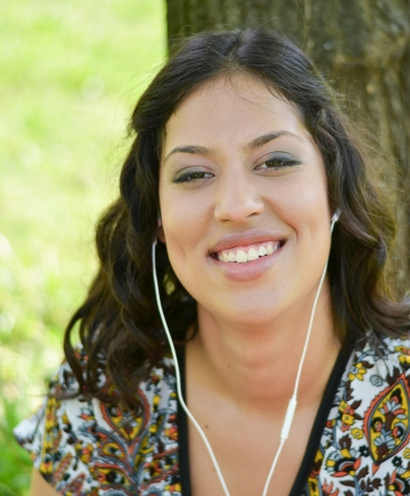 Beautiful smiling woman listening to music outdoors photo