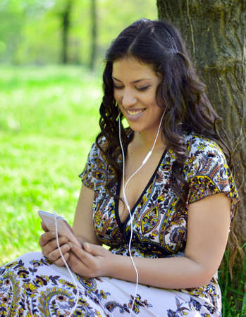 leaned: Beautiful woman listening to music outdoors Stock Photo
