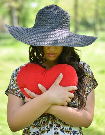 Portrait of girl holding big red heart outdoors photo
