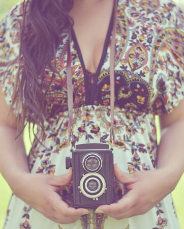 Retro image of woman hands holding vintage camera outdoors photo