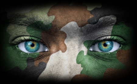 Soldier face with army colors looking from dark Stock Photo