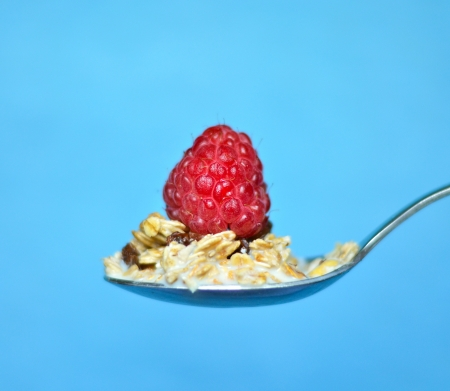 Spoon with muesli and one juicy raspberry closeup shot photo