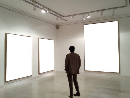 Man in gallery room looking at empty frames Banque d'images