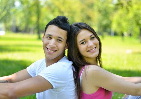 Happy young couple back to back in park photo