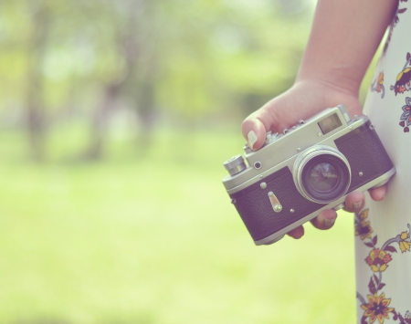 camera lens: Close up of woman hand holding retro camera Stock Photo
