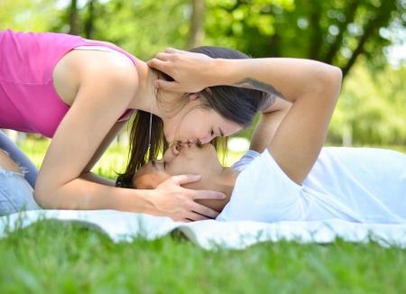 besos hombres: Feliz pareja de jóvenes en el parque besándose en la hierba Foto de archivo