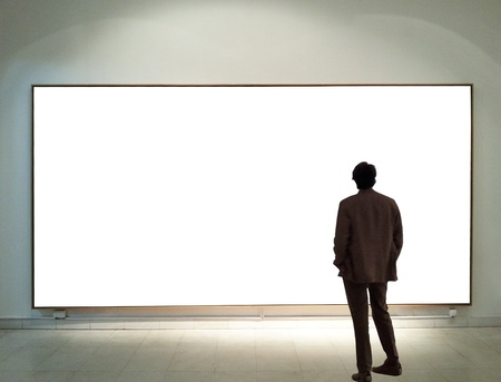 Man in gallery room looking at empty frames photo