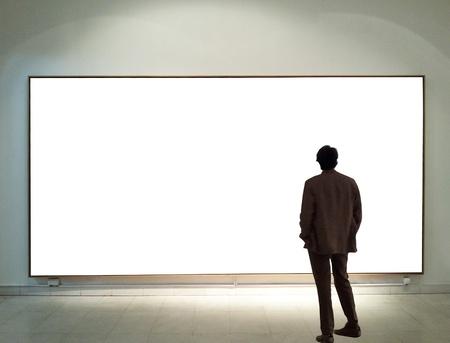 blank billboard: Man in gallery room looking at empty frames Stock Photo