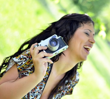 Smiling woman holding vintage camera photo