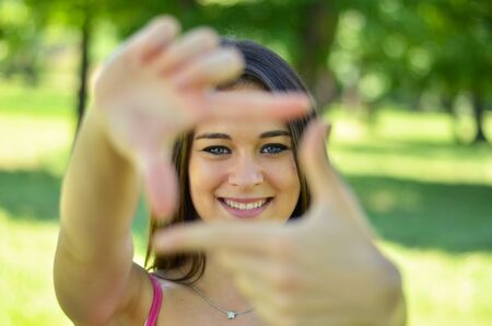 Beautiful girl making frame with hands while outdoors  photo