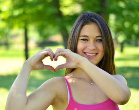 Cute teen girl making heart shape with her hands outdoors photo