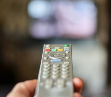 television set: Hand holding remote controller with tv in the background