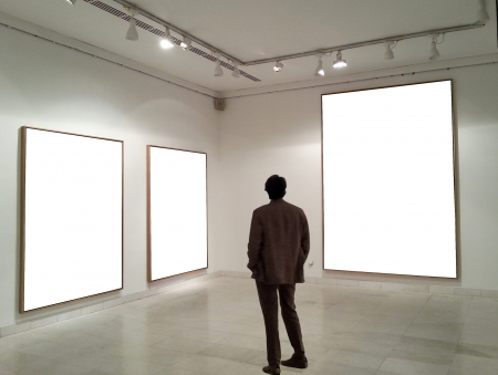 Man in gallery room looking at empty frames Stock Photo