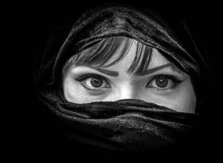 purdah: Portrait of beautiful Arab woman with brown eyes wearing black scarf in black and white