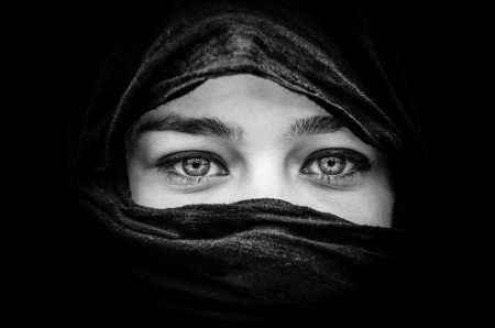 purdah: Portrait of beautiful woman with blue eyes wearing black scarf in black and white Stock Photo