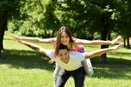 Portrait of flying happy beautiful couple outdoors with spread hands Standard-Bild