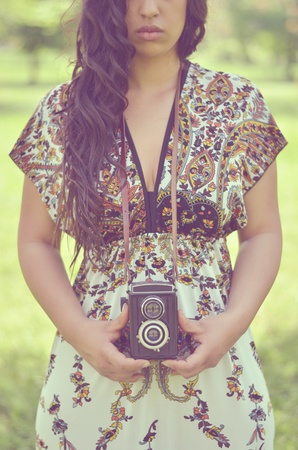Retro image of beautiful woman holding vintage camera outdoors Stock Photo - 21051806