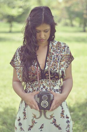 Retro image of beautiful woman holding vintage camera outdoors photo