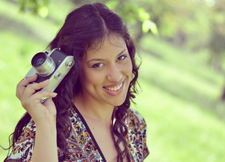Retro image of beautiful woman holding vintage camera photo