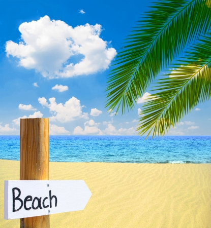 Paradise beach and sea with wooden board showing direction to the beach photo