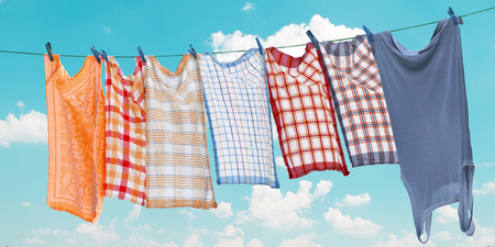 Laundry hanging over clear blue sky Stock Photo