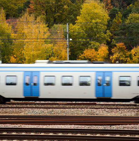 Fast train against Autumn forest photo