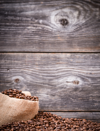 Coffee background - Sack of coffee grains against grunge wood background photo