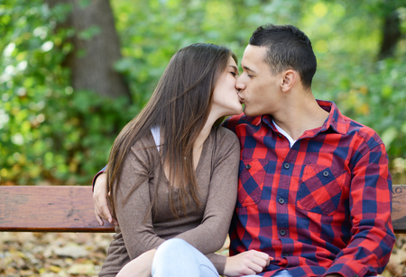 Couple kissing at the bench in park photo