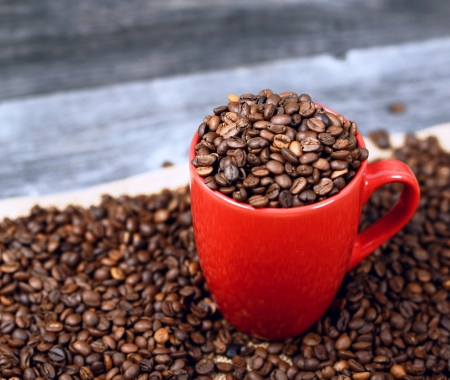 Cup of coffee filled with coffee beans against wooden background photo