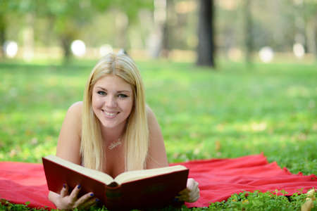 Happy smiling woman reading book in park photo
