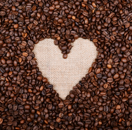 Heart coffee frame made of coffee beans on burlap background photo