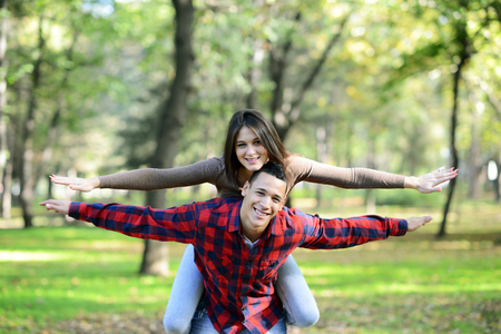 Portrait of flying happy beautiful couple outdoors with spread hands photo
