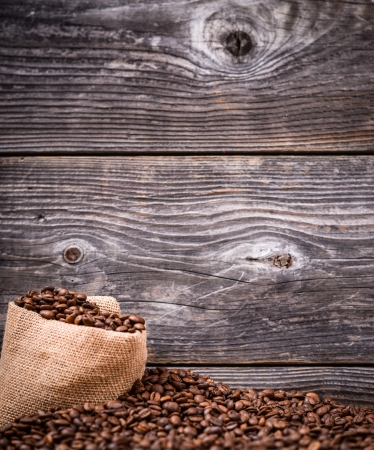 finite: Sack of coffee grains against wooden background Stock Photo